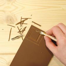 1. Konturen mit den Schneidefedern vorsichtig herausheben: Den Griff der Schneidefedern wie ein Messer halten und nicht zu tief in die Druckplatte schneiden. Langsam arbeiten, um Verletzungen zu vermeiden! Druckplatte abputzen.