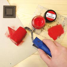 2. Stoffmalfarbe mit dem Farbroller auf der Glasplatte verteilen, bis der Farbroller gleichmäßig mit Farbe bedeckt ist. Mit dem Farbroller die Farbe gleichmäßig auf die Druckplatte auftragen. Ein Probedruck auf Zeitungspapier ist zu empfehlen.