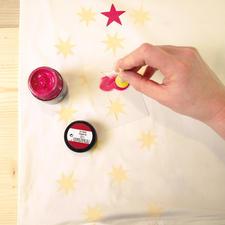 2. Stoffmalfarbe direkt aus dem Glas mit einem Schwammstupf-Pinsel aufnehmen und am Glasinnenrand abstreifen. Schablone mit der Farbe gleichmäßig austupfen. Danach sofort die Schablone abziehen